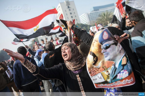 A woman holds up a poster of Field Marshall Abdel Fattah Al-Sisi during the third anniversary of the January 25 revolution.