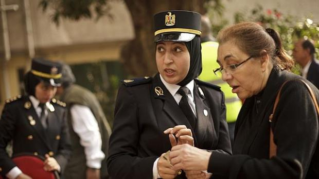 An Egyptian policewoman directs a woman at a polling station during voting on Egypt's latest constitution in 2014. Credit: AP